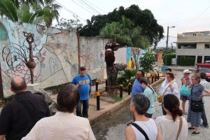 """A man in a blue shirt that says, """"Cuba"""" stands in front of a mural and two metal sculpures, talking to a group"""