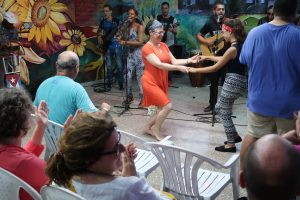 A woman in an orange dress dances with a young girl in front of a 5-person live band and a wall covered in mural
