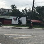 "A sign with an image of Fidel Castro reading ""Fidel entre nosotros"""