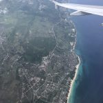 The Cuban coastline from the air, with the tip of a plane wing on the upper right