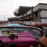 Several classic cars in the road leading to the airport entrance
