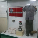 Museum display of a uniform, flag, lantern, plaque, and book