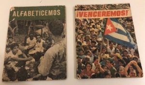 Two booklets, one titled Alfabeticemos and the other titled Venceremos. The covers each have photos of young Cubans.