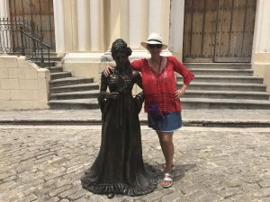 A woman stands next to the bronze statue of another woman