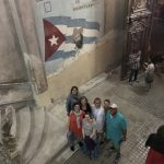 7 people look up from the bottom of a large stone staircase. A Cuban flag is painted on the wall behind them.