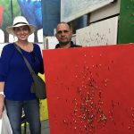 A man and woman stand behind a large red painting covered with small figures of people