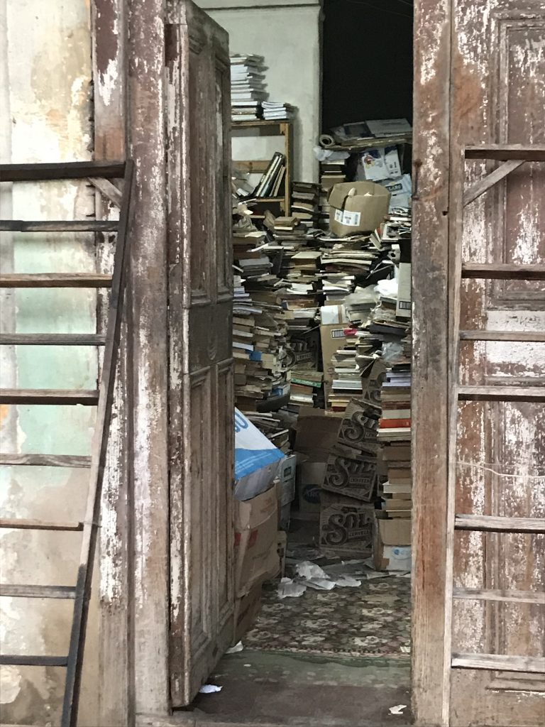 Books piled high in stacks inside a narrow entrance